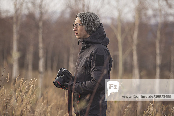 'Photographer with a camera and standing in a field  Alaska  Autumn '