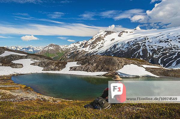 Hiker rests alongside a lake while hiking the Harding Icefield Trail  Kenai Fjords National Park  Kenai Peninsula  Southcentral Alaska