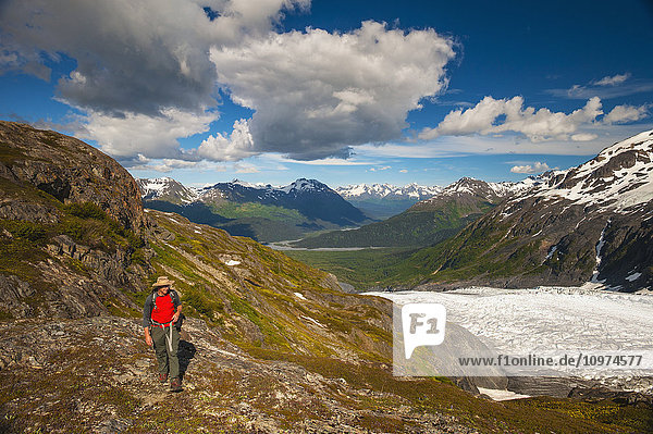 A man hiking near the Harding Icefield Trail with the Chugach Mountains and the Resurrection Valley in the background  Kenai Fjords National Park  Southcentral Alaska