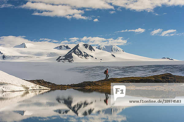 A man hiking by a lake with the Harding Icefield and the Nunatak peaks in the background  Kenai Fjords National Park  Southcentral Alaska