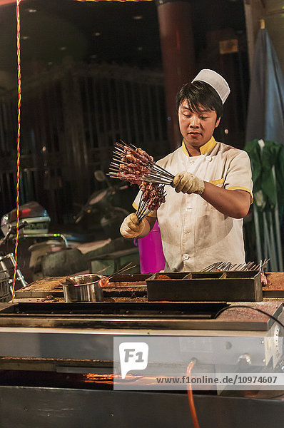 'A Muslim Man Preparing Some Mutton In His Traditional Barbecue; Xian  Shaanxi Province  China'