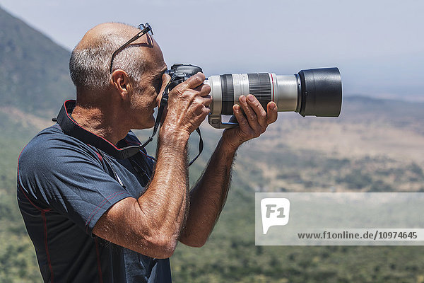 'A balding man is photographing a view of the Rift Valley in the sunshine using a digital SLR camera with a long lens; Tharaka Nithi  Kenya'