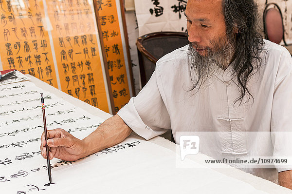 'A Chinese man writes characters in his street shop; Xian  Shaanxi province  China'