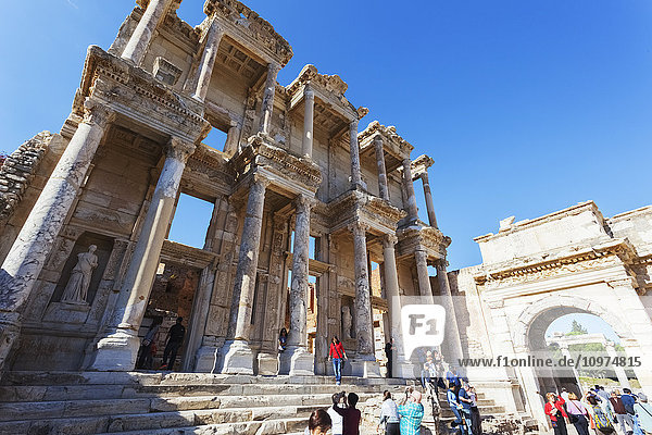 'Tourists at the ruins of the Celsus Library  a monumental tomb for Gaius Julius Celsus Polemaeanus; Ephesus  Izmir  Turkey' 'Tourists at the ruins of the Celsus Library, a monumental tomb for Gaius Julius Celsus Polemaeanus; Ephesus, Izmir, Turkey'