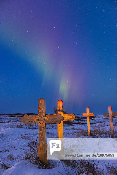 The aurora borealis colors the sky above crosses catching the light of dusk at Cemetery Hill in Kotzebue  Alaska.