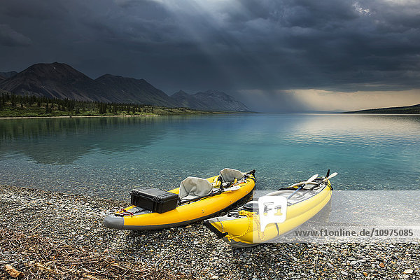 A pair of yellow inflatable kayaks on the Lower Twin Lake beach with a summer thunderstorm in the background  Lake Clark National Park & Preserve  Southcentral Alaska.