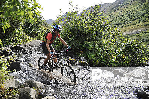 Woman rides a full suspension mountain bike across a stream on the Devil's Pass Trail in the Chugach National Forest  Kenai Peninsula  South-central Alaska