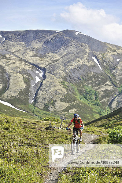 Woman rides a full suspension mountain bike on the Resurrection Pass Trail in the Chugach National Forest  Kenai Peninsula  South-central Alaska