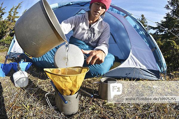 Woman backpacker prepares coffee at camp near Upper Fuller Lake in the Kenai National Wildlife Refuge on the Kenai Peninsula in South-central Alaska