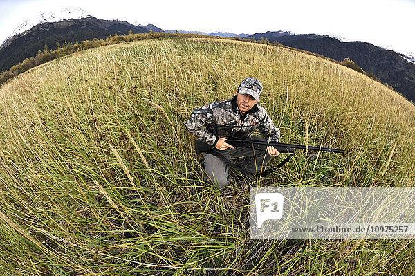 Duck hunter waits in tall grass with a shotgun in the Chugach Mountains of South-central Alaska  Autumn