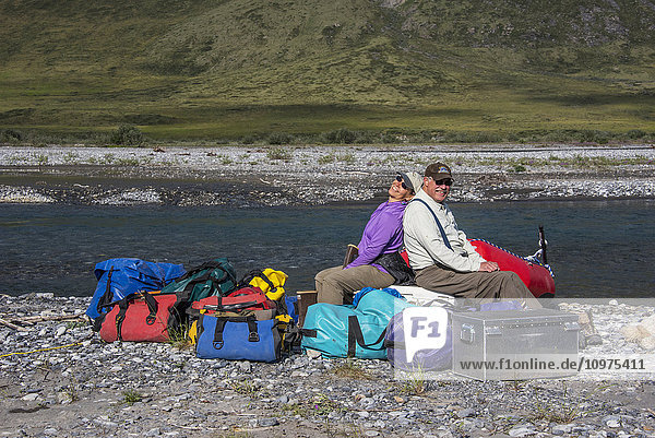 Rafters sitting on pile of gear in the sun along the Canning River in the Arctic National Wildlife Refuge  Summer  Alaska