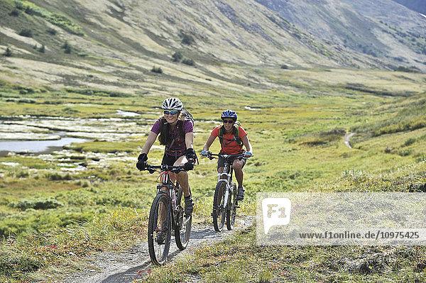 Women ride full suspension mountain bikes on the Resurrection Pass Trail in the Chugach National Forest  Kenai Peninsula  Southcentral Alaska