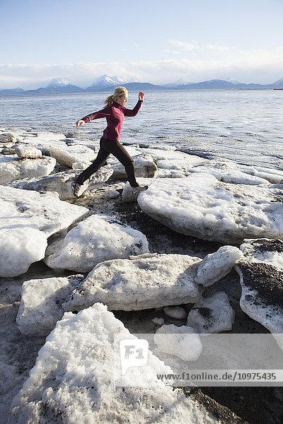 Woman running on the ice covered beach in Homer  Kenai Peninsula  Southcentral Alaska