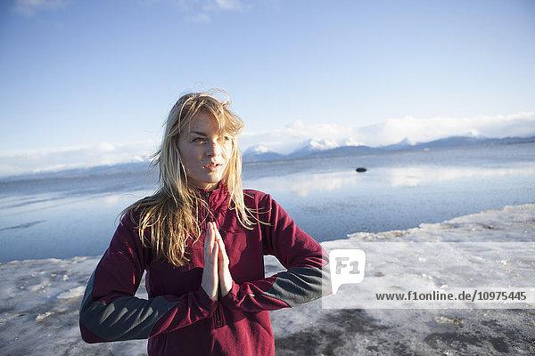 Woman an icy beach before a run on the Homer beach  Kenai Peninsula  Southcentral Alaska