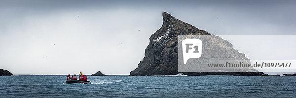 'Inflatable cruises towards jagged rock at sea; Antarctica'