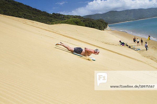 'Sand Boarding the Hokianga Sand Dunes on the Tasman Sea; Hokianga  New Zealand'