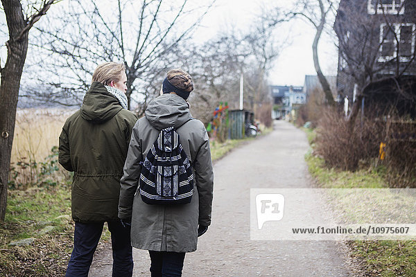 'A couple walks down a path in the bohemian neighbourhood of Christianshavn  where residents consider their community to be a separate entity apart from Copenhagen; Christianshavn  Denmark'