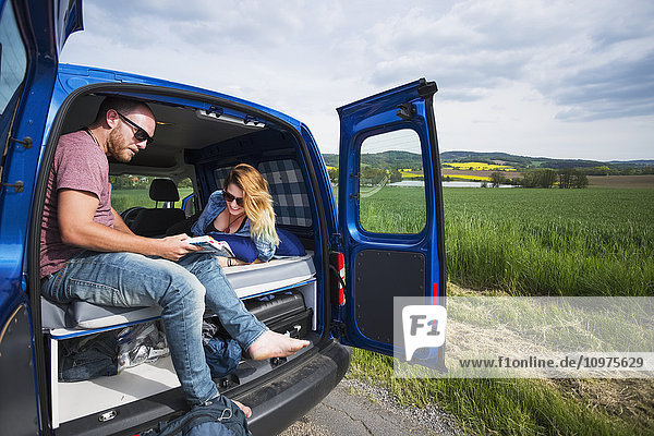 'A quick rest stop along the road  a couple sits in the back of a camper van with the doors open; Czech Republic'
