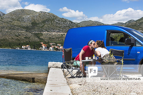'A couple shares a kiss outside their camper van at a beach along the coast; Slano  Croatia'