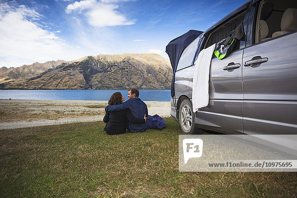 'A couple sits outside their camper van at Kidds Bush campsite at Lake Hawea; Hunter Valley  Otago  New Zealand'