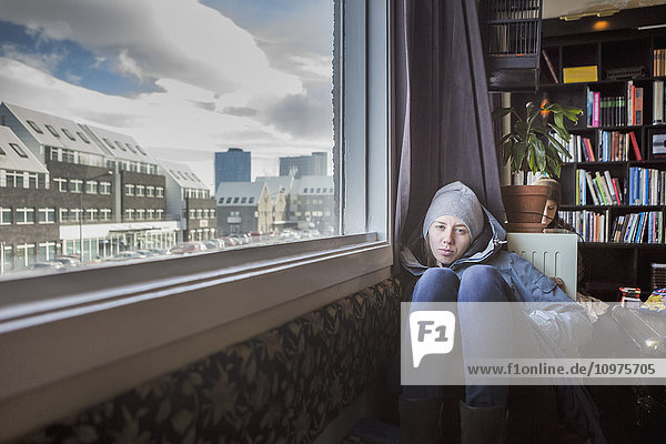 'A girl sits on the floor of an apartment with a view out the window; Reykjavik  Iceland'