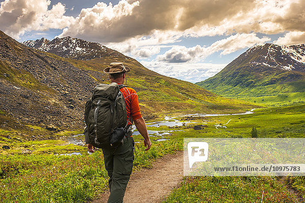 Man hikes the Reed Lakes Trail in Archangel Valley  Talkeetna Mountains  Southcentral Alaska  summer