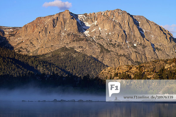 'Woman sits on rock and views sunrise over June Lake  Mono Basin; California  United States of America'