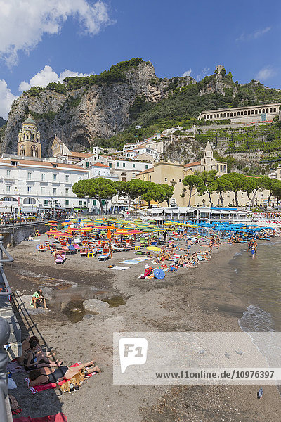 'A beach view of the town of Amalfi on the Amalfi Coast in Italy  with the tourists lying on the beach and the village buildings and mountains in the background; Amalfi  Province of Salerno  Italy'