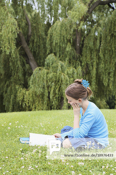 'Girl sitting in park reading a book; Toronto  Ontario  Canada'