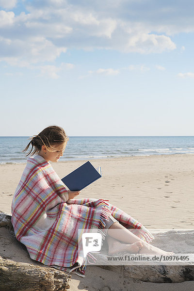 'Girl wrapped in a blanket sitting on a log on beach reading a book; Toronto  Ontario  Canada'