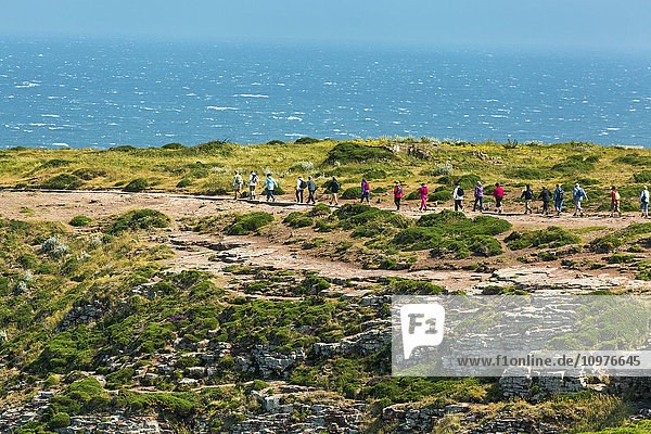 'Several walkers along a stone pathway overlooking the sea with blue sky; Frehal  Brittany  France'