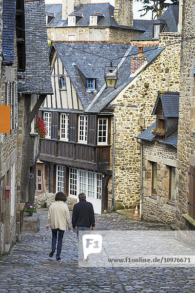 'Couple walking down a cobblestone road framed with old stone buildings; Dinan  Brittany  France'