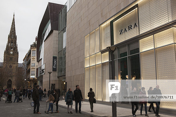 'Shoppers in the commercial district of the city centre next to a branch of Zara with the cathedral spire behind; San Sebastian  Spain'