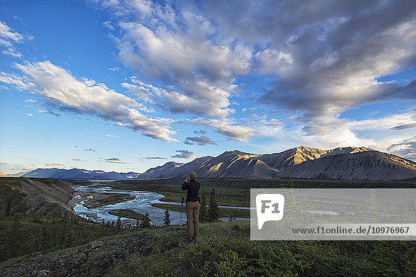 'Woman taking pictures while looking out at the Wind River in the Peel Watershed; Yukon  Canada'