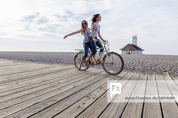 'Two girls riding double on a single bike on a beach boardwalk; Toronto  Ontario  Canada'