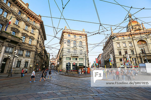 'This popular tourist road is intersected by the lines of the electric buses and tram cars that carry tourists to sightseeing desitantions down the cobblestone streets in historic Milan; Milan  Italy'