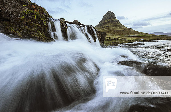 'Kirkjufell is seen here as a waterfall flows in front of the camera  Snaefellsness peninsula; Iceland'
