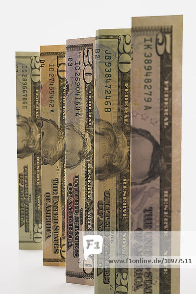 Upright And Folded Us Currency Bank Notes On A White Background  Studio Composition