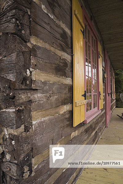 Partial View Of The Logs And The Veranda On An Old Canadiana (Circa 1825) Cottage Style Residential Log Home  Quebec  Canada. This Image Is Property Released For Calendar  Book  Magazine And Editorial Use Only. Lupr0176
