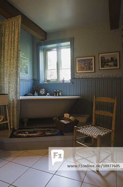 Antique Chair And Roll Top Bathtub On An Elevated Platform In The Main Bathroom Of An Old Canadiana (Circa 1741) Cottage Style Wooden Siding Residential Home  Quebec  Canada. This Image Is Property Released For Calendar  Book  Magazine And Editorial Use O