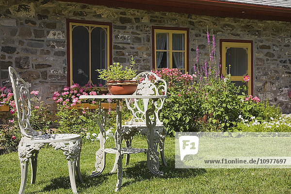 White Cast Iron Garden Chairs And Table On The Front Lawn Of An Old French Regime (Circa 1794) Cottage Style Residential Fieldstone Home  Quebec  Canada  This Image Is Property Released For Calendar  Book  Magazine And For Editorial Use Only. Lupr0153