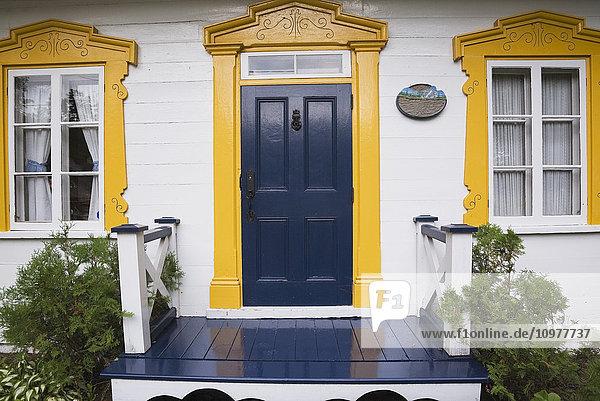 Close-Up Of The Front Entrance Door And Person On An Old Canadiana (Circa 1830) Cottage Style Cedar Shingle And Wooden Siding Residential Home  Quebec  Canada. This Image Is Property Released For Calendar  Book  Magazine And Editorial Use Only. Lupr0152