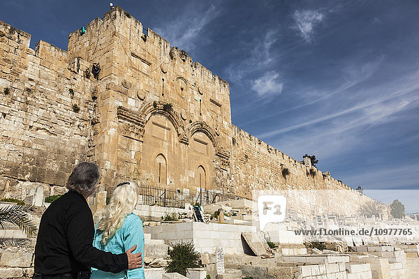 'A couple stands looking at the Eastern gate of the Temple Mount  Old city Jerusalem; Jerusalem  Israel'