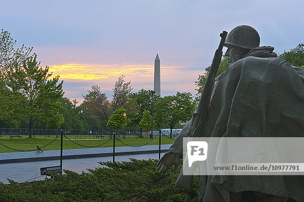 'The statue of a soldier looks to the side at the Korean War Veterans Memorial in Washington  D.C. with the Washington Monument in the background; Washington  District of Columbia  United States of America'
