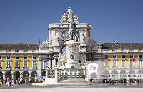 Tourists Walking Across The Praca Do Commercio (Commerce Square) With The Statue Of King Jose I And Rua Augusta Arch In The Background  Lisbon  Portugal  Europe