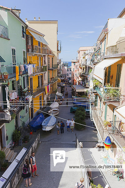 'Looking down at the residences with clothes lining their balconies and a view of the shops and tourists on the streets of Manarola; Manarola  Liguria  Italy'