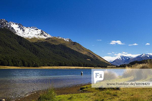 'A man practices fly fishing at Mavora Lake; Mavora  Southland  New Zealand'