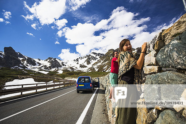 'A couple holding on to a rock wall along the Great St. Bernard Pass  one of the most ancient passes through the Western Alps  going through Italy and Switzerland; Italy'