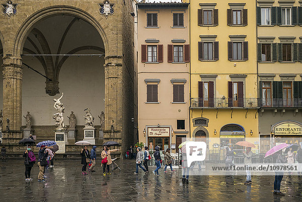 'Pedestrians in a town square on a rainy day; Florence  Italy'
