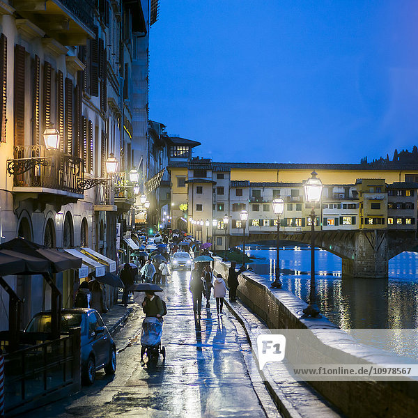'Pedestrians walking on a wet promenade at dusk along the Arno River with a view of Ponte Vecchio; Florence  Italy'